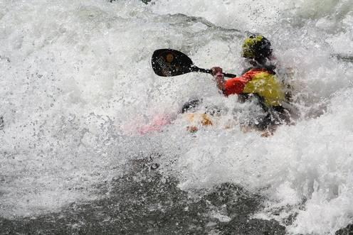 Kajak-Fahrer kämpft sich durch wildes Gewässer
