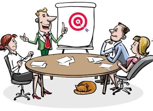 vier Personen arbeiten am Tisch sitzend vor Chart mit Dartscheibe (Zielorientierung)