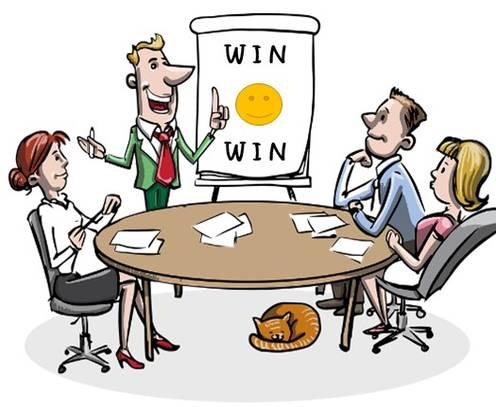 Gründerteam arbeitet am Tisch sitzend vor Chart mit Dartscheibe (Zielorientierung)