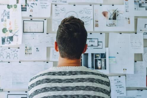 Mann steht vor Pinnwand mit vielen Zetteln